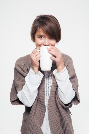 knitted jacket: Pretty smiling young woman in knitted jacket drinking tea from big white mug over white background