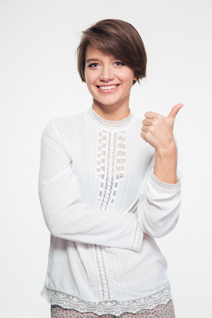 short haircut: Happy attractive young woman with short haircut showing thumbs up over white background Stock Photo