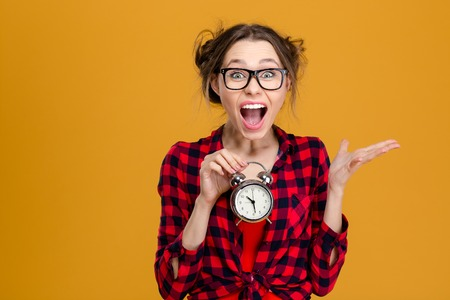 Amusing pretty young woman in plaid shirt and glasses holding alarm clock and shouting over yellow background Stockfoto