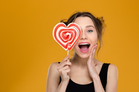 Happy excited young woman covered her eye with bright heart shaped lollipop over yellow background Stock Photo