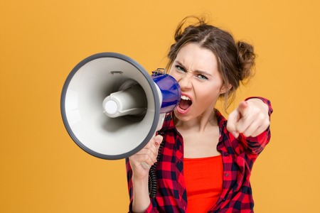 Annoyed furious young woman in checkered shirt shouting in loudspeaker and pointing on you over yellow background