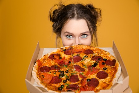 Lovely cute positive young woman hiding behind pizza over yellow background
