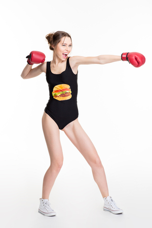 Excited funny young woman in black designer swimwear and red boxing gloves making direct hit and shouting over white background