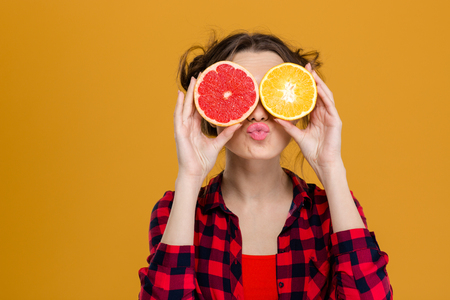 woman eating fruit: Funny playful young woman in checkered shirt holding halves of citrus fruits against her eyes and making duck face over yellow background
