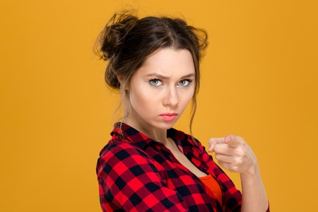 irritated: Close up portrait of angry irritated young woman in plaid shirt pointing on you over yellow background Stock Photo