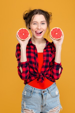 flirty: Flirty smiling young woman in checkered shirt and jeans shorts winking and posing with two halves of grapefruit over yellow background Stock Photo
