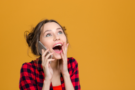 shoked: Charming surprised content young woman in plaid shirt talking on cell phone over yellow background Stock Photo