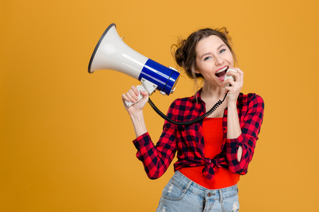 Portrait of a young casual woman screaming in megaphone over yellow background Banco de Imagens