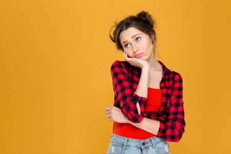 women jeans: Portrait of sad depressed beautiful young woman in plaid shirt over yellow background