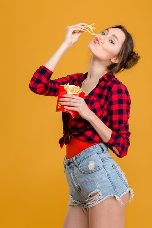 Amusing comical cute young woman in plaid shirt and jeans shorts having fun with french fries over yellow background