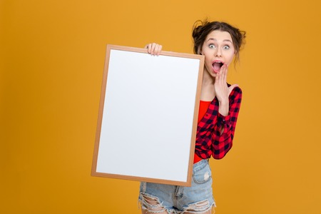 board shorts: Amazed happy young woman in checkered shirt and jeans shorts holding blank board over yellow background
