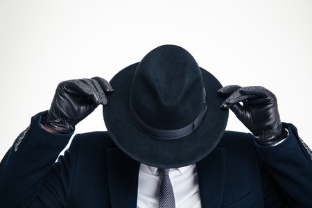 gangster: Closeup of black hat weared on business person in black suit and holded by hands in modern black gloves over white background