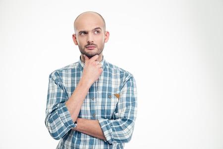 Aantrekkelijke doordachte jonge man in geruite overhemd op zoek weg over witte achtergrond