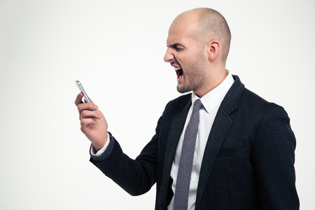 Angry mad young businessman holding mobile phone and screaming over white background