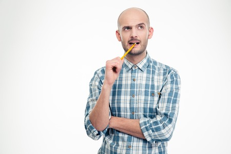 man think: Pensive handsome young male in plaid shirt with pencil in his mouth isolated over white background