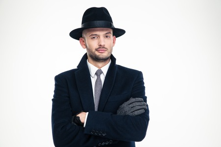 Confident handsome business man in coat, hat and gloves standing over white background