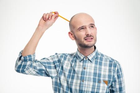 思いやりのある魅力的若い男が白い背景の上 pensil によって彼の頭を悩ま