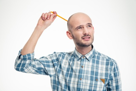 Thoughtful attrative young man scratching his head by pensil over white background