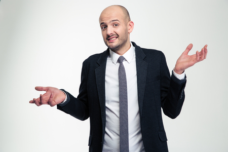 Confused embarrassed young businessman holding copyspace on both palms over white background Imagens