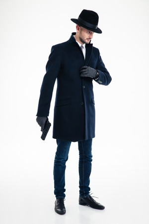 Full length of concentrated thoughtful man in black coat, hat and gloves standing and holding gun over white background