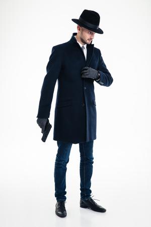 Volledige lengte van de geconcentreerde nadenkende mens in zwarte laag, hoed en handschoenen die en kanon zich over witte achtergrond bevinden houden Stockfoto