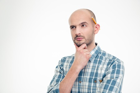 human ear: Portrait of concentrated thoughtful young man in checkered shirt with pencil behind ear isolated over white background
