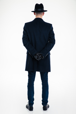overcoat: Back view of business man in black clothes and hat standing over white background