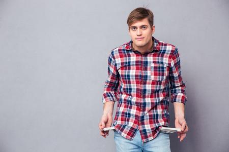 apuesto joven pobre en camisa de cuadros y pantalones vaqueros que muestran los bolsillos vacíos sobre fondo gris