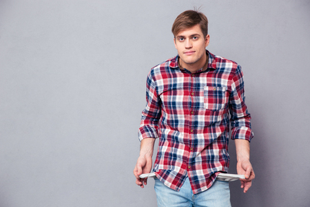 Poor handsome young man in checkered shirt and jeans showing empty pockets over grey background Foto de archivo