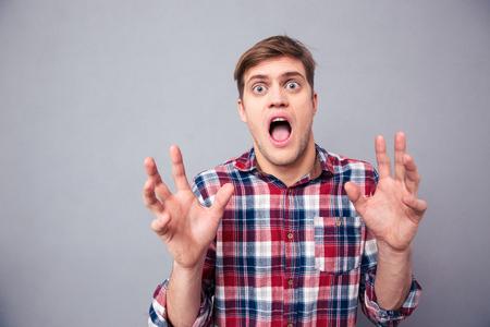 Ritratto di terrorizzato spaventata giovane in camicia a scacchi urlando con la bocca aperta su sfondo grigio