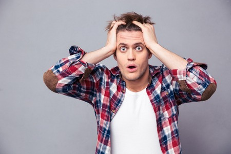 expressive face: Shocked dazed young man in plaid shirt holding head with both hands over grey background
