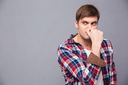 detestable: Irritated handsome young man in plaid shirt covered his nose because of bad smell over grey background