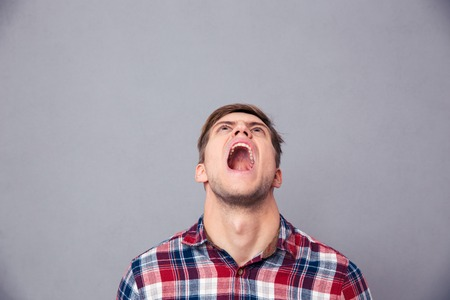 Despaired angry young man in plaid shirt looking up and screaming over grey background Stock Photo