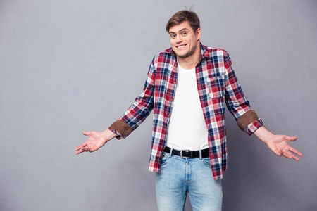 Confused cute young man in plaid shirt and jeans standing and shrugging over grey background Foto de archivo