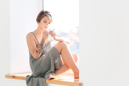 Beautiful pensive young woman with tatoo on hand sitting on window-sill and drinking coffee