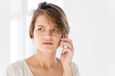 disturbed: Worried disturbed young woman talking on mobile phone over white background