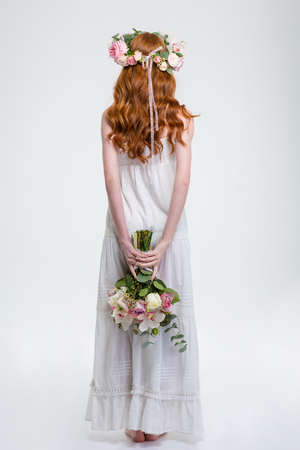 Back view of young woman with long red hair in white sundress and wreath standing and hiding bouquet of flowers behind her back over white background