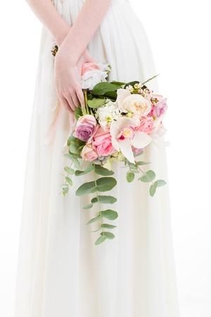 cropped image: Closeup portrait of a woman in white dress holding flowers