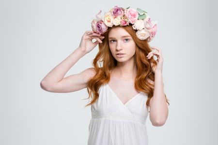 Chiuda in su di bella giovane donna con capelli rossi ricci in corona di fiori e girasole bianco su sfondo bianco
