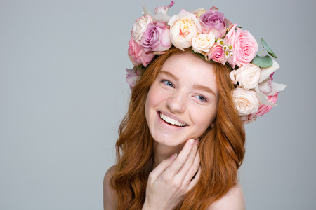 Close up portrait of charming cheerful young woman with long red hair in beautiful flower wreath