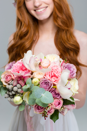 cropped image: Cropped image of a smiling redhead woman holding flowers