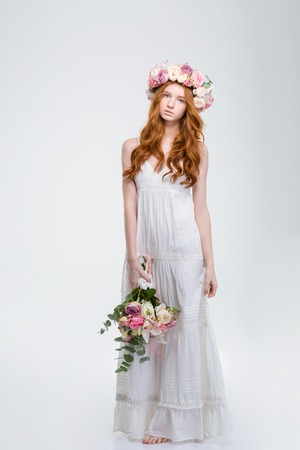 barefoot: Full length of beautiful young redhead woman in white sundress and wreath standing barefoot and holding bouquet of flowers over white background