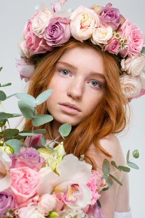 flower head: Close up portrait of beautiful young redhead woman in wreath of roses with flowers bouquet over white background Stock Photo