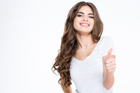Portrait of a happy charming woman showing thumb up isolated on a white background Stock Photo