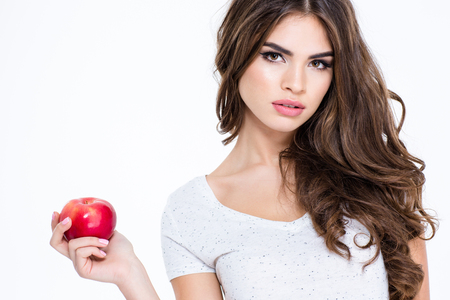 Portrait of a young charming woman holding apple isolated on a white background and looking at camera