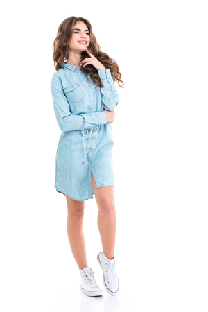 Full length of cheerful attractive young woman in blue casual dress and white sneakers over white background Фото со стока