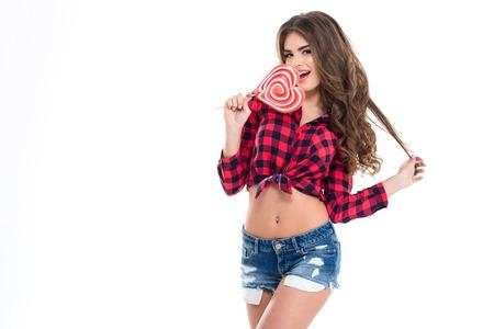 Charmante jeune femme heureuse avec de longs cheveux bouclés en chemise et jean damier short manger coeur sucette en forme sur fond blanc