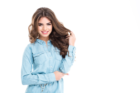 tenderness: Happy beautiful young woman in blue jeans shirt playing with her hair over white background