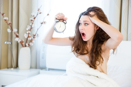 Stressed woman waking up with alarm