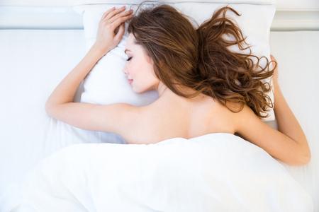 modelos desnudas: relajado mujer joven hermosa con el pelo largo que miente y que duerme en cama en el dormitorio Foto de archivo